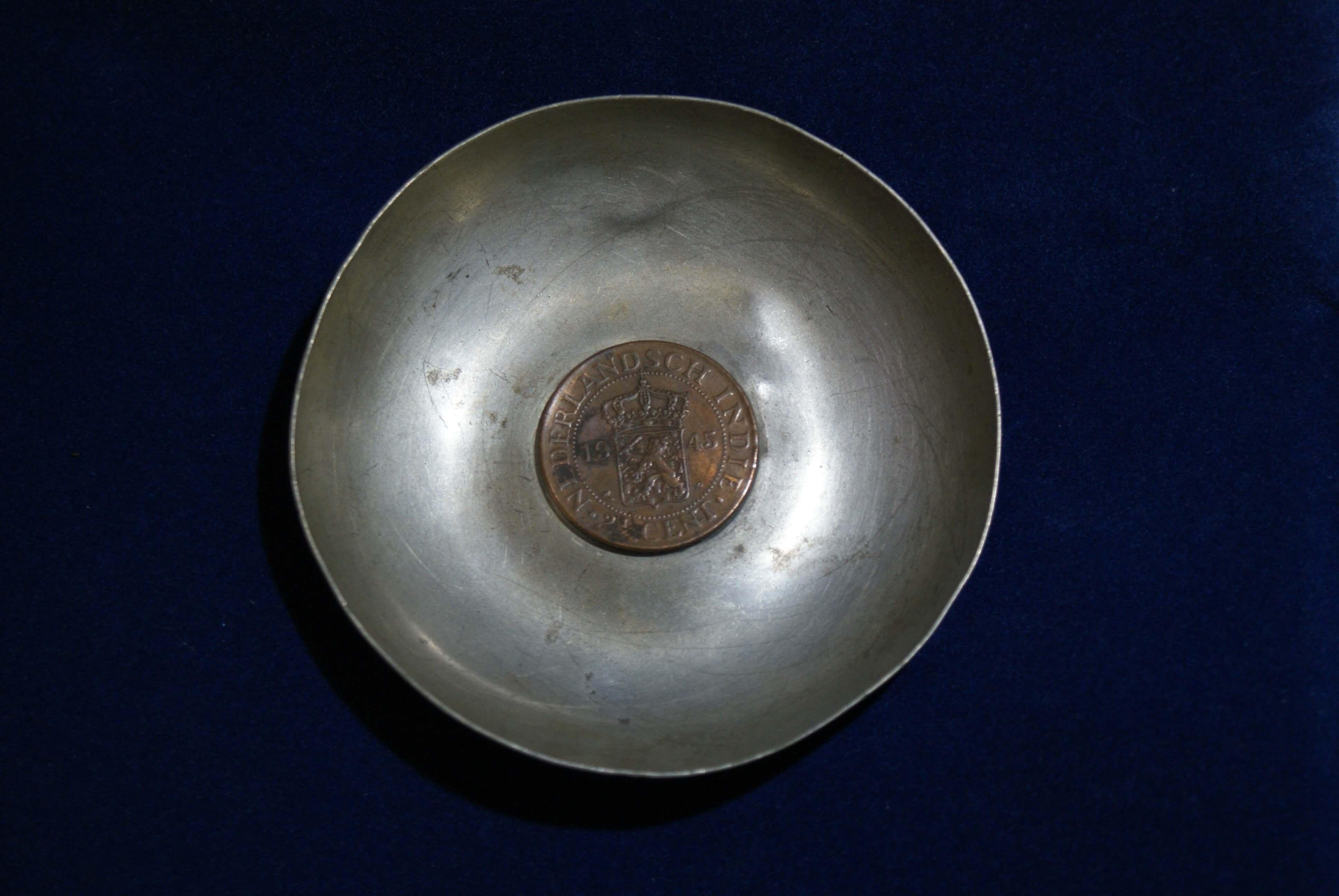 Asbak met een munt uit Nederlands-Indië.